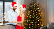 love and holidays concept - happy couple in santa hats hugging over home room with christmas tree background