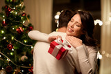 winter holidays and people concept - happy couple with christmas gift hugging at home - 229897691