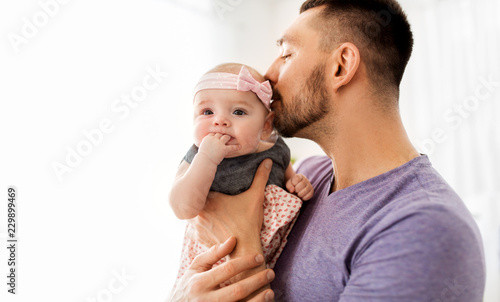 Leinwandbild Motiv family, fatherhood and people concept - close up of happy father kissing little baby daughter