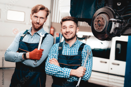 Leinwanddruck Bild Two Automechanics Posing With Wrenches In Garage.