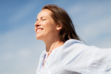 people and leisure concept - happy smiling woman enjoying sun - 229899655