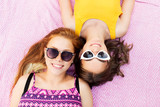 summer fashion, eyewear and people concept - smiling teenage girls in sunglasses lying on picnic blanket - 229902063