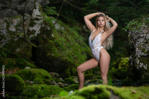 Blonde woman posing in white underwear in the middle of the forest - 229909832
