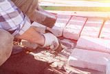 working hands lay brick masonry in cement mortar