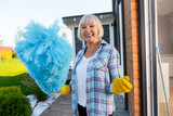 Doing cleaning. Beaming emotional blonde-haired elderly lady doing cleaning near summer house - 229916615
