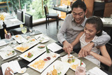 Smiling father helping his daughter with her dish while they eating lunch at restaurant - 229919628