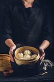 Woman presenting dim sum dumplings in steamer