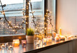 Leinwanddruck Bild - hygge, decoration and christmas concept - candles burning in lanterns and festive garland on window sill at home