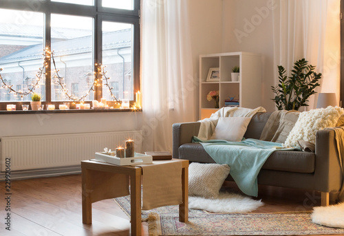 interior, christmas and interior concept - cushioned sofa, coffee table, garland string and candles on window sill in living room of cozy home © Syda Productions