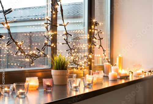 Leinwanddruck Bild hygge, decoration and christmas concept - candles burning in lanterns and festive garland on window sill at home