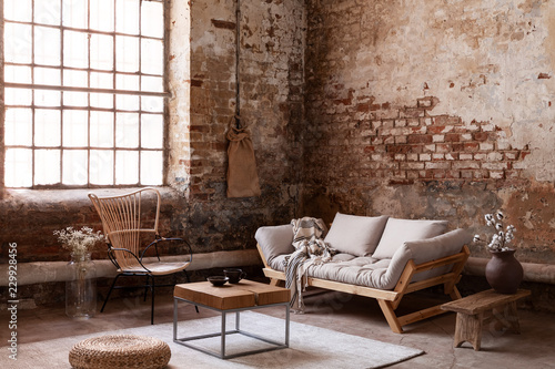 Armchair in beige couch in living room interior in wabi sabi style with flowers on table and window. Real photo