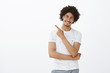 Door is there. Portrait of friendly happy male photographer in stylish t-shirt with afro hairstyle and moustache, tilting head and smiling broadly while pointing at upper left corner over grey wall
