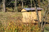 Apiary, wooden and wicker hand made traditional old beehives in a green garden - 229933428