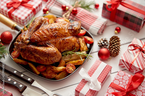 Roasted whole chicken or turkey served in iron pan with beautiful Christmas decoration. Placed on white rustical wooden background. Top view. - 229936082