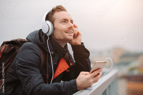 Smiling man in headphones enjoy listening to music outdoors in city rooftop - 229942243