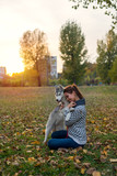Beautiful young woman hugging her Husky dog outside