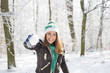 Leinwandbild Motiv Beautiful young woman playing with a snowball outside in a forest