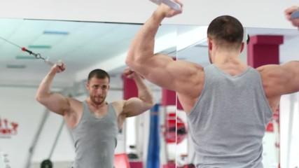 Young muscular man hard training in gym © sokolan