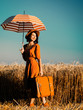 portrait of the beautiful young woman with red umbrella and brown suitcase standing on the field