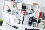 A young man sitting at a computer Desk in the office and raised his hands up. - 230008802