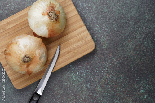Onions On A Bamboo Cutting Board With A Knife Sitting On A