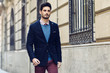 Attractive man wearing british elegant suit in the street. Modern hairstyle.