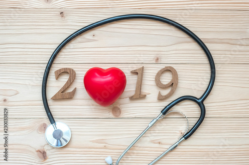 Leinwanddruck Bild 2019 Happy New Year for healthcare, Wellness and medical concept. Stethoscope with red heart and wooden number on table background
