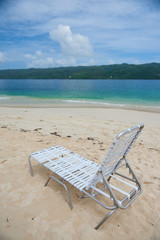 Small plastic deck chair standing on sand of Cayo Levantado beach against beautiful water of Atlantic Ocean in the Samana Bay. Lounge is white and lightwaight. water is blue and sky has some clouds.