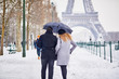 Couple of tourists walking in Paris on a day with heavy snow