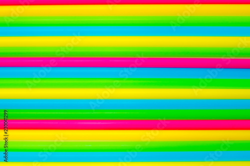 Leinwandbild Motiv Colorful background. Vivid flatlay. Multicolored plastic drinking cocktail straws on a white background.