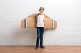 Boy playing with cardboard airplane wings on his back points finger at you - 230049220