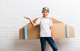 Boy playing with cardboard airplane wings on his back holding copyspace imaginary on the palm - 230049410
