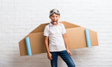 Boy playing with cardboard airplane wings on his back showing tongue at the camera having funny look