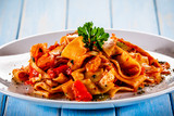 Pasta with tomato sauce and vegtables on wooden table