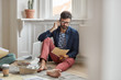 People and business concept. Unshaven male employee thinks on better solution, talks via smart phone, reads documentation, sits bare foot, solves problems, discuss working process, plan organization