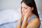 Head pain. Attractive young woman wake up on her bed looking unhappy and feeling sick. - 230071414