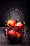 Basket with apples on rustic wooden table
