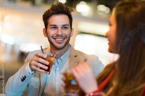 Couple toasting glasses in a disco - 230113229