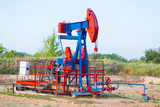 The oil pump, industrial equipment. Oil field site, oil pumps are running. Rocking machines for oil production in a private sector.