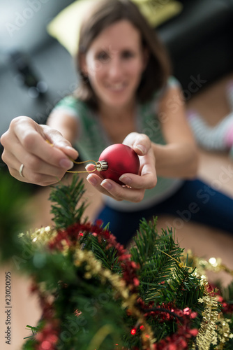 Young woman placing re bauble on christmas tree - 230120095