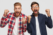 Indoor shot of overjoyed guys clench fists with happiness, have happy expressions, dressed in casual clohtes, isolated over white background. Two stylish bearded hipsters celebrate their triumph