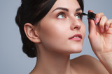 Beautiful woman applying mascara tenderly - 230124696