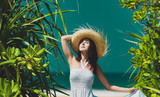 Portriat of Young redhead woman in a hat and white dress near the ocean - 230137007