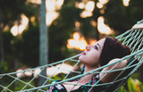 Young redhead woman in a bikini relaxing in a hammock in sunset time - 230137097