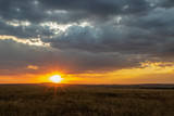 African landscape at sunset with starburst sun, tall grass and dark clouds