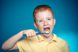 Boy is brushing his teeth. Happy child kid boy brushing teeth. Smiley boy without one teeth with toothbrush isolated on blue background. Shirt design, health, oral hygiene. - 230151215