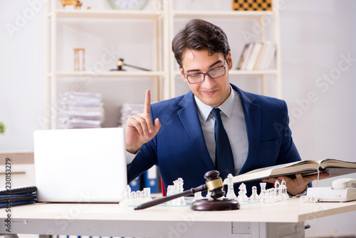 Leinwanddruck Bild Young lawyer playing chess to train his court strategy and tacti