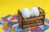 White eggs in a wooden crate, on a patchwork rug, with yellow background. - 230154006