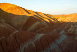 Rainbow Mountains at sunset in China's Zhangye Danxia Landform Geological Park. Layers of different colored sandstone and minerals were pressed together and then buckled up by tectonic plates. - 230173050