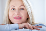 Active beautiful middle-aged woman smiling friendly and looking in camera. Woman's face closeup. Realistic images without retouching with their own imperfections. Selective focus. - 230220441